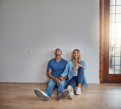 Buy stock photo Shot of a young couple sitting on the floor in their new home