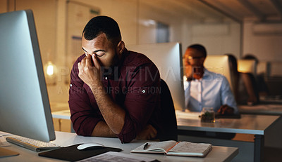 Buy stock photo Shot of a young businessman looking stressed out while working late in an office