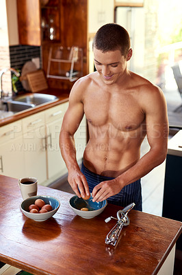 Buy stock photo Cropped shot of a handsome young shirtless man making breakfast in the kitchen at home