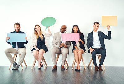 Buy stock photo Full length portrait of a group of business colleagues holding up blank signs and placards while sitting in their office