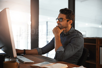 Buy stock photo Shot of a young businessman working late on a computer in an office
