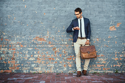 Buy stock photo Full length shot of a handsome young businessman checking the time while standing against a grey facebrick wall