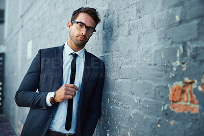 Buy stock photo Cropped portrait of a handsome young businessman standing against a grey facebrick wall