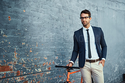 Buy stock photo Cropped shot of a handsome young businessman standing with his bicycle against a grey facebrick wall