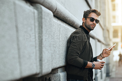 Buy stock photo Cropped shot of a handsome young man sending a text while traveling through the city