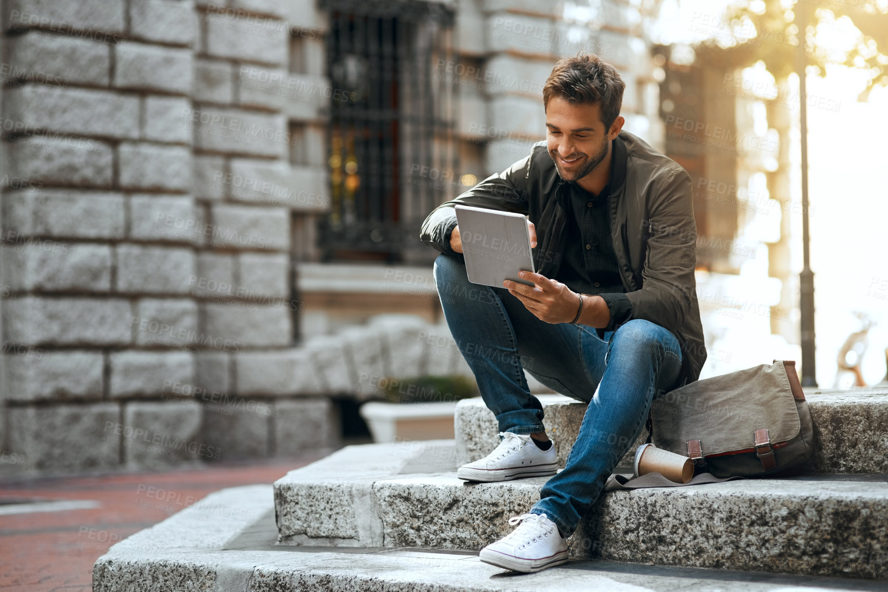 Buy stock photo Full length shot of a handsome young man using his tablet while traveling through the city