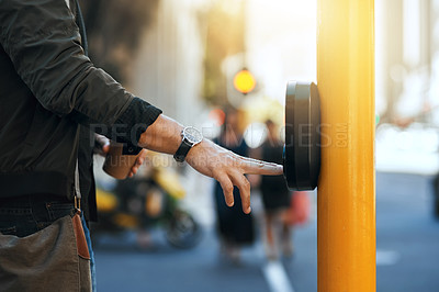 Buy stock photo Cropped shot of an unrecognizable man pressing the crosswalk button on a traffic light while traveling through the city