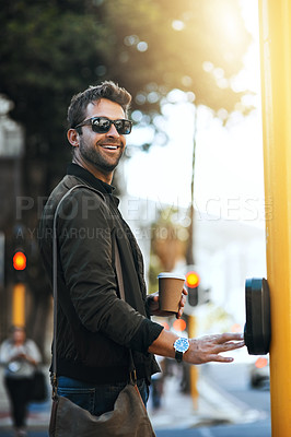 Buy stock photo Cropped shot of a handsome young man pressing the crosswalk button on a traffic light while traveling through the city