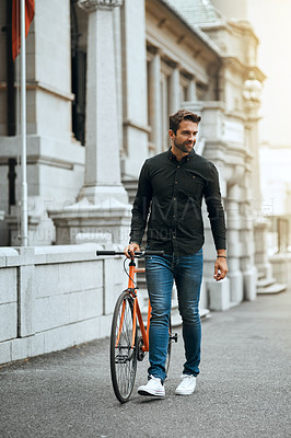 Buy stock photo Full length shot of a handsome young man traveling with his bike through the city