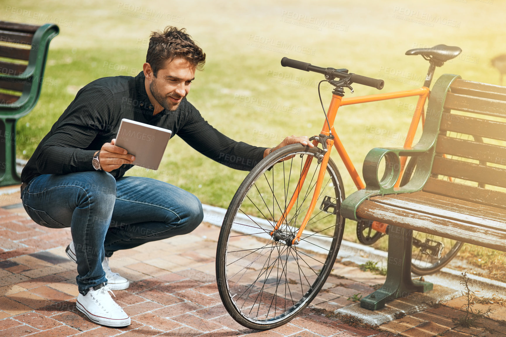 Buy stock photo Full length shot of a handsome young man using his tablet while in the park