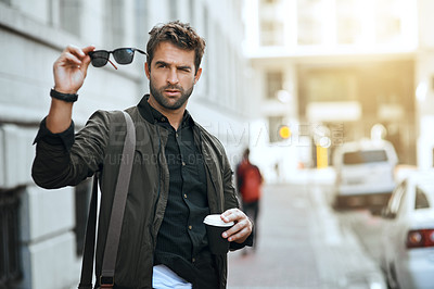 Buy stock photo Cropped shot of a handsome young man checking his sunglasses while traveling through the city