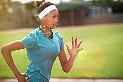 Buy stock photo Shot of an athletic young woman listening to music while running on the track