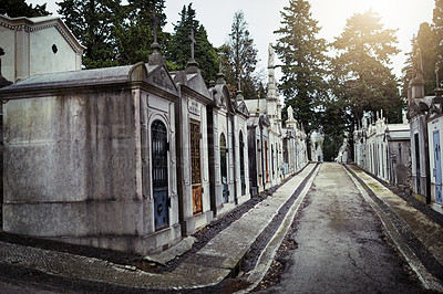 Buy stock photo Shot of a row of graves situated next to each other inside of a graveyard outside during the day