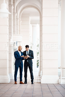Buy stock photo Shot of young handsome businessmen using a cellphone together outside