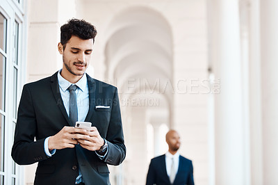 Buy stock photo Cropped shot of a young handsome businessman using a cellphone outside
