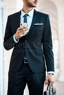 Buy stock photo Cropped shot of an unrecognizable businessman using a cellphone outside