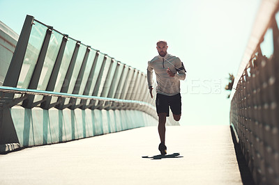 Buy stock photo Shot of a handsome young man running on a bridge in the city