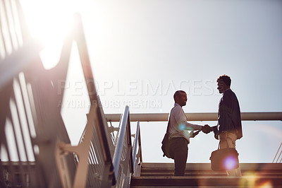 Buy stock photo Low angle shot of young handsome businessmen shaking hands on top of a staircase outside