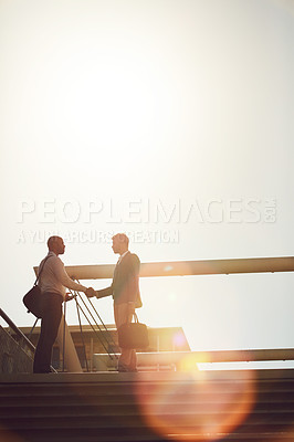 Buy stock photo Low angle shot of two businessmen shaking hands on top of a staircase outside