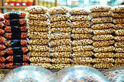 Buy stock photo Shot of packets full of nuts stacked on top of each other ready to be sold at a market during the day
