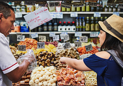 Buy stock photo Shot of a cheerful young woman browsing through a market while buying some treats from a shop owner