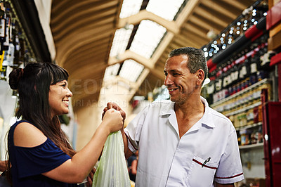 Buy stock photo Shot of a cheerful young woman receiving goods she just bought at a market during the day