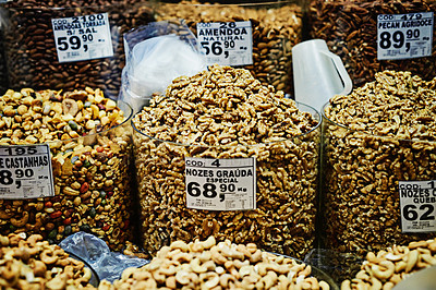 Buy stock photo Shot of containers filled with different types of nuts and put on display to be sold at a market during the day
