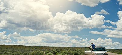 Buy stock photo Shot of a young man getting out of his car to look at the view on a road trip