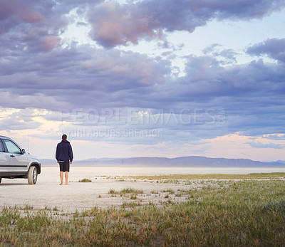 Buy stock photo Shot of a young man looking at the view on a desert road trip