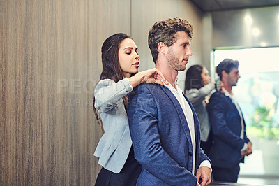 Buy stock photo Cropped shot of a businesswoman adjusting a businessman's collar in an elevator