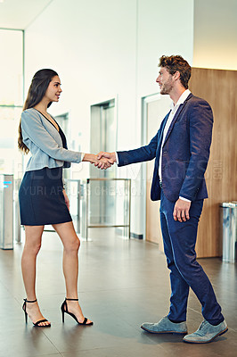 Buy stock photo Shot of a businessman and businesswoman greeting by handshake in a lobby