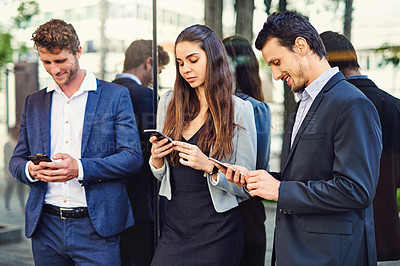 Buy stock photo Cropped shot of businesspeople using cellphones outside