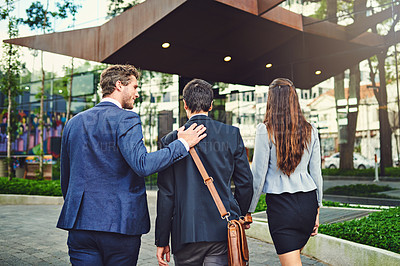 Buy stock photo Rearview shot of unrecognizable businesspeople walking to a building together outside