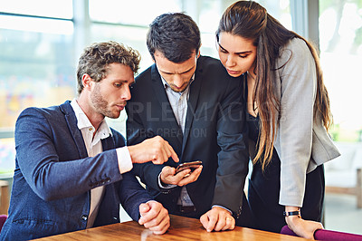 Buy stock photo Cropped shot of businesspeople using a cellphone together indoors