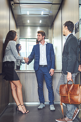 Buy stock photo Shot of businesspeople meeting and greeting in an elevator