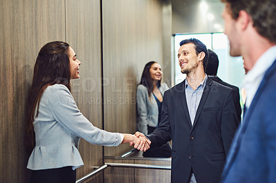 Buy stock photo Cropped shot of businesspeople meeting and greeting in an elevator