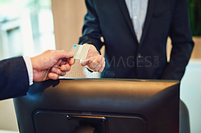 Buy stock photo Cropped shot of an unrecognizable businessman checking in and paying with a credit card in a hotel