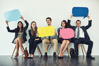 Buy stock photo Studio shot of a group of businesspeople holding colorful speech bubbles while waiting in line