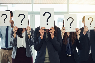 Buy stock photo Shot of a group of businesspeople holding questions marks in front of their faces
