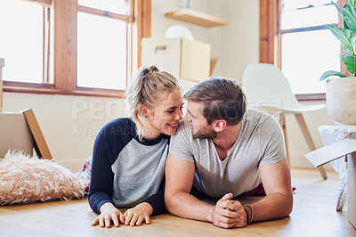 Buy stock photo Cropped shot of a happy young couple being affectionate while lying on the floor in their new home