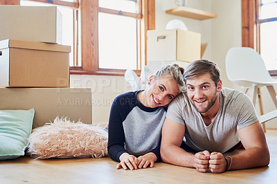 Buy stock photo Portrait of a happy young couple lying on the floor in their new home