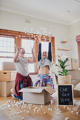 Buy stock photo Shot of a happy young couple being playful with boxes in their new home