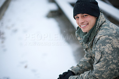 Buy stock photo Shot of a young soldier sitting outside on a snowy day