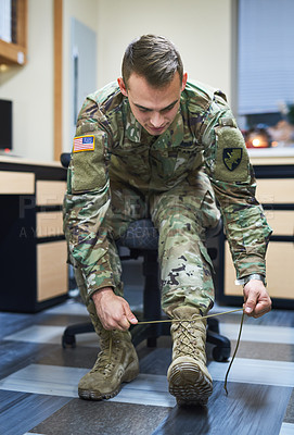 Buy stock photo Shot of a young soldier tying his boot shoelaces in the dorms of a military academy