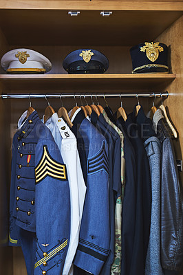 Buy stock photo Shot of various military jackets and hats hanging in a closet
