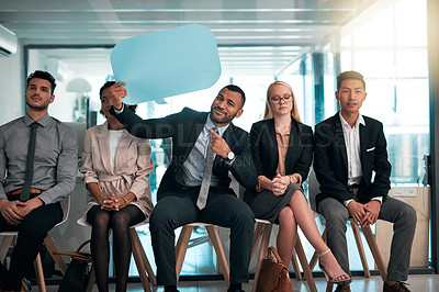 Buy stock photo Portrait of a handsome young businessman holding up blank placards while sitting in the office with his colleagues