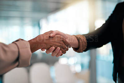 Buy stock photo Cropped shot of two unrecognizable businesswomen shaking hands while standing in their office