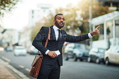 Buy stock photo Shot of a handsome young businessman gesturing to get a cab in the city