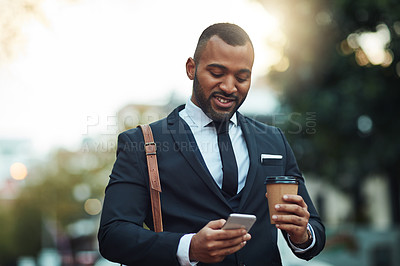 Buy stock photo Shot of a young businessman using his cellphone while walking outside
