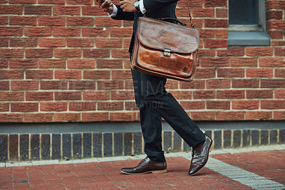 Buy stock photo Cropped shot of an unrecognizable business walking with his briefcase in the city